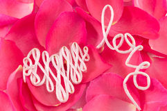 Amour de Word fait en fil sur des pétales de rose Photographie stock libre de droits