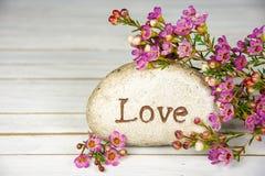 Amour de Word sur la pierre avec des fleurs Photographie stock