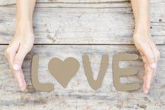 Amour de Word sur le bois avec la main de femme Photo libre de droits