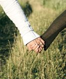 Amour Deux mains avec les anneaux le jour du mariage en vert gentil ont réservé le fond Image stock