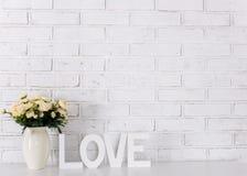 Amour en bois blanc, fleurs et espace de mot au-dessus du mur de briques blanc Photos stock
