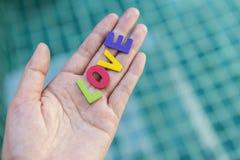 Amour en bois coloré sur la main de fille Images stock