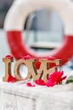 Amour en bois découpé de mot parmi les pétales de rose roses sur le fond Image stock