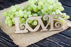 AMOUR en bois d'inscription et raisins verts Photo stock