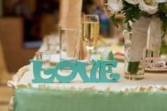 Amour en bois de lettres sur des jeunes mariés de table de mariage Photo stock
