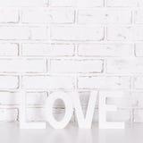 Amour en bois de mot au-dessus du mur de briques blanc Image stock
