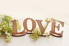 Amour en bois de mot avec des lis et endroit pour votre texte Photographie stock