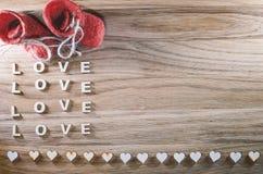 Amour en bois de mot et le coeur sur un fond rustique Chaussures rouges Images stock