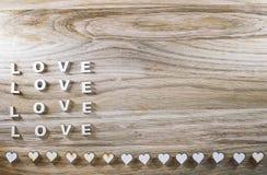 Amour en bois de mot et le coeur sur un fond rustique Le jour de Valentine Photos stock