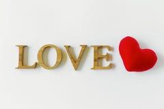 Amour en bois et coeur rouge sur le fond blanc Image stock