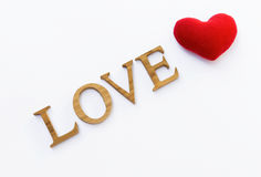 Amour en bois et coeur rouge sur le fond blanc Photos stock