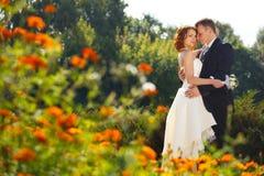Amour en fleurs - support de jeunes mariés parmi le marigol français Image stock