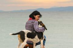 Amour et amitié entre un propriétaire de chien de femme et son chien contre la mer Photographie stock libre de droits