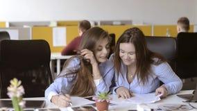 Amour et bavardage dans le bureau Les filles parlent au-dessus d'un garçon banque de vidéos