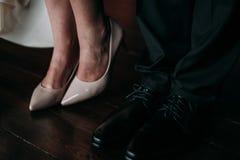 Amour et bonheur le jour du mariage Le plan rapproché du ` s de jeune mariée et les pieds du ` s de marié et les chaussures et le Image stock