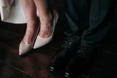 Amour et bonheur le jour du mariage Le plan rapproché du ` s de jeune mariée et les pieds du ` s de marié et les chaussures et le Photos libres de droits