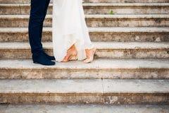 Amour et bonheur le jour du mariage Plan rapproché du ` s de jeune mariée et des pieds du ` s de marié Photos libres de droits