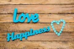 Amour et bonheur - mots en bois de turquoise bleue avec le shap de coeur Photos stock