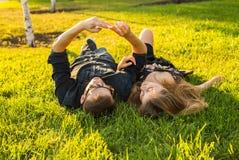 Amour et concept de personnes - couple adolescent heureux se trouvant sur l'herbe et prenant le selfie sur le smartphone à l'été Image stock