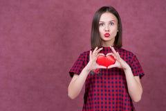 Amour et femme de jour de valentines jugeant le sourire de coeur mignon et adorable d'isolement sur le fond rose Photo stock
