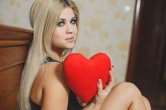 Amour et femme de jour de valentines tenant le coeur se reposant sur le plancher dans une chambre à coucher. Belle femme blonde da Photo libre de droits