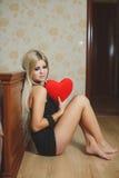 Amour et femme de jour de valentines tenant le coeur se reposant sur le plancher dans une chambre à coucher. Belle femme blonde da Photos libres de droits