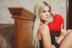 Amour et femme de jour de valentines tenant le coeur se reposant sur le plancher dans une chambre à coucher. Belle femme blonde da Photographie stock