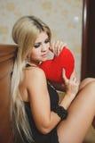 Amour et femme de jour de valentines tenant le coeur se reposant sur le plancher dans une chambre à coucher. Belle femme blonde da Image libre de droits