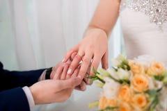 Amour et mariage Cérémonie de mariage du marié mettant l'anneau d'or sur le doigt du ` s de jeune mariée Images libres de droits