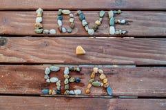 Amour et mer de mots écrits avec des cailloux Photos libres de droits