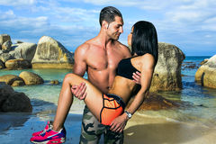 Amour et muscles sur la plage de rochers Photo stock