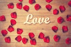 Amour et pétales de Word sur la table en bois Images libres de droits