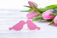 Amour et romance Jour heureux du `s de Valentine Deux oiseaux et tulipes roses sur un fond clair L'espace libre Photo stock