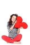 Amour et Saint-Valentin, une femme tenant un coeur rouge. Belle femme de brune dans l'amour. Photos stock