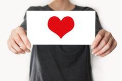 Amour. Femelle dans la chemise noire montrant ou tenant une carte Photos libres de droits