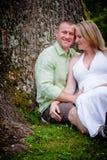 Amour : Futurs parents s'asseyant sous un arbre Image stock