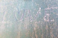 Amour gelé sur la fenêtre de voiture avec la forme de coeur sur le pare-brise givré Images libres de droits