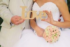 Amour - inscription en bois pour épouser dans les mains des jeunes mariés Photographie stock libre de droits