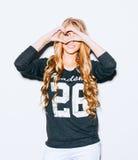 Amour Jeune femme heureuse de sourire de portrait avec de longs cheveux blonds, faisant le signe de coeur, symbole avec le fond b Photos libres de droits