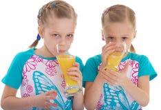 Amour jumel de soeurs pour boire du jus d'orange. Images libres de droits