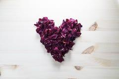 Amour Les pétales de rose sont rayés sous forme de coeur sur la table Photos stock