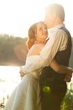 Amour lumineux - le couple de mariage étreint derrière un lac Photos stock