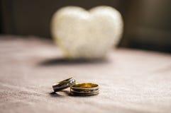 Amour, mariage et concept de jour de ` s de Valentine Beaux anneaux de mariage d'or et foyer sélectif de coeur en verre Utile com Image stock