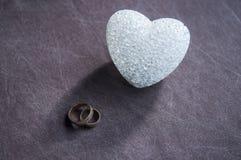 Amour, mariage et concept de jour de ` s de Valentine Beaux anneaux de mariage d'or et foyer sélectif de coeur en verre Utile com Photo libre de droits