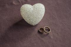 Amour, mariage et concept de jour de ` s de Valentine Beaux anneaux de mariage d'or et foyer sélectif de coeur en verre Utile com Photos libres de droits