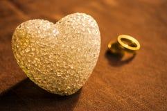 Amour, mariage et concept de jour de ` s de Valentine Beaux anneaux de mariage d'or et foyer sélectif de coeur en verre Utile com Photographie stock libre de droits