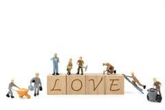 Amour miniature de mot de renforcement d'équipe de travailleur sur le fond blanc Image libre de droits