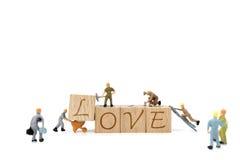 Amour miniature de mot de renforcement d'équipe de travailleur sur le fond blanc Photos stock
