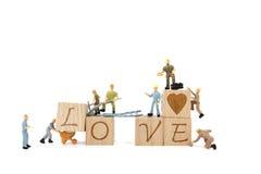 Amour miniature de mot de renforcement d'équipe de travailleur sur le fond blanc Photographie stock