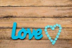 Amour - mot en bois de turquoise bleue avec le ruban de marguerite de forme de coeur Photographie stock